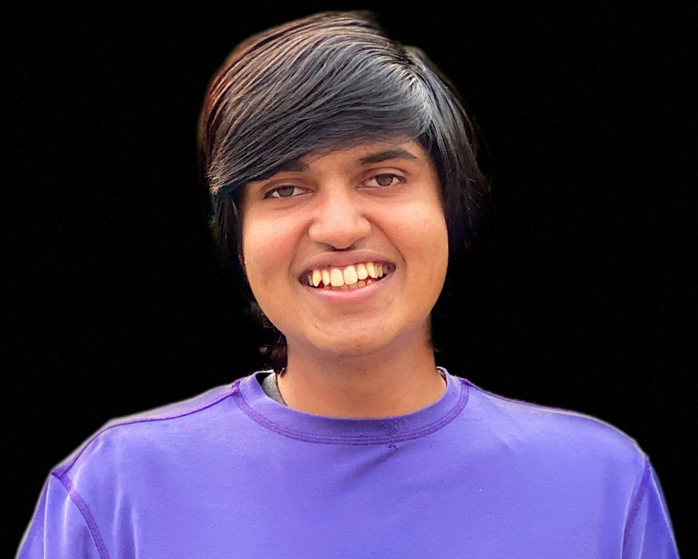 vardhan agrawal smiling in a square profile photo with black background and purple t-shirt